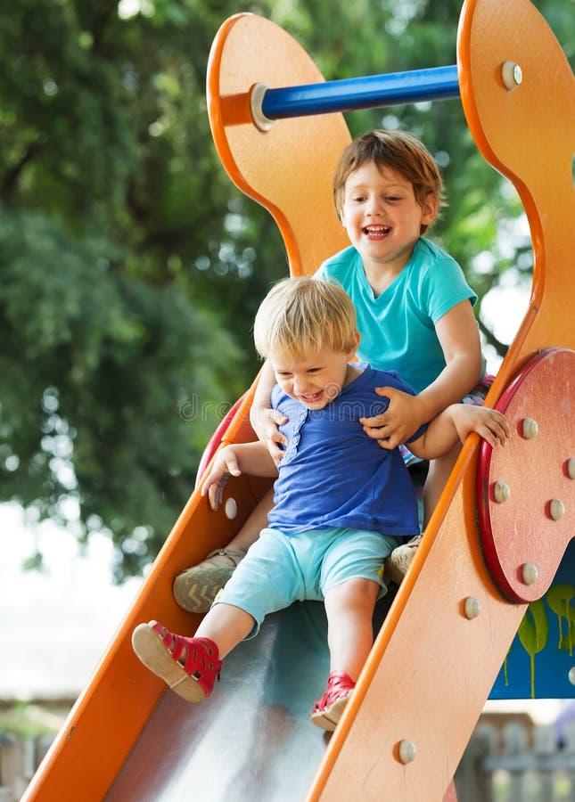 Crianças felizes no campo de jogos imagem de stock