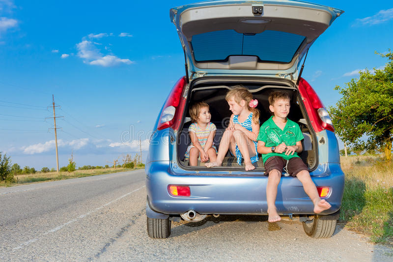 crianças felizes no carro, viagem da família, curso das férias de verão imagem de stock