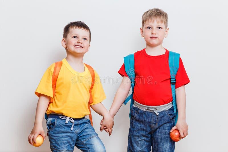 Crianças felizes nos t-shirt e nas calças de brim com as trouxas no fundo branco imagens de stock royalty free