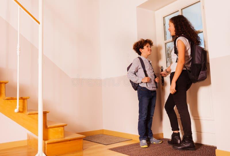 Crianças felizes que abrem a porta que sae à escola fotografia de stock royalty free