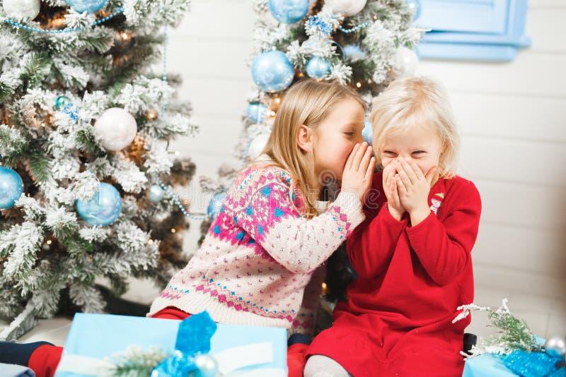 Crianças felizes que abrem presentes na Noite de Natal fotos de stock