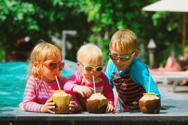 Crianças felizes que bebem o cocktail do coco na estância de verão imagem de stock