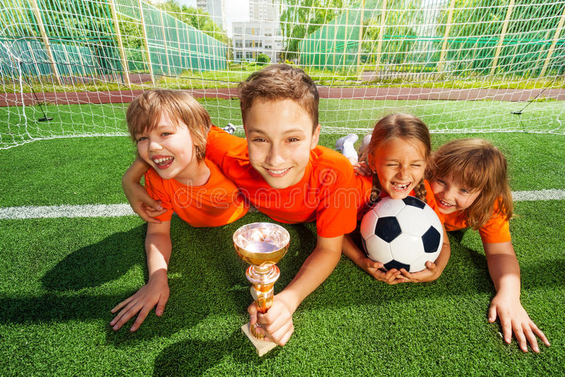 Crianças felizes que colocam na grama com cálice dourado fotografia de stock royalty free