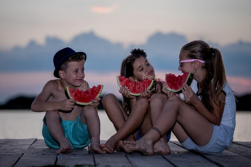 Crianças felizes que comem a melancia no tempo do por do sol fotos de stock
