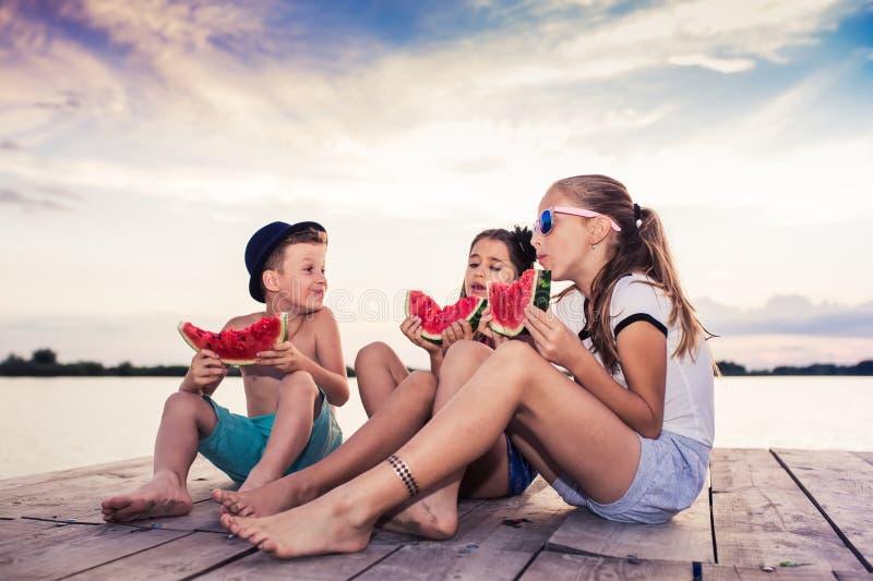 Crianças felizes que comem a melancia no tempo do por do sol fotografia de stock