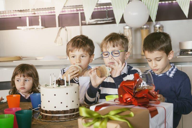 Crianças felizes que comemoram em torno de um bolo para um aniversário fotografia de stock