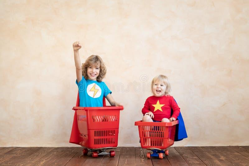 Crianças felizes que conduzem o carro do brinquedo em casa imagem de stock royalty free