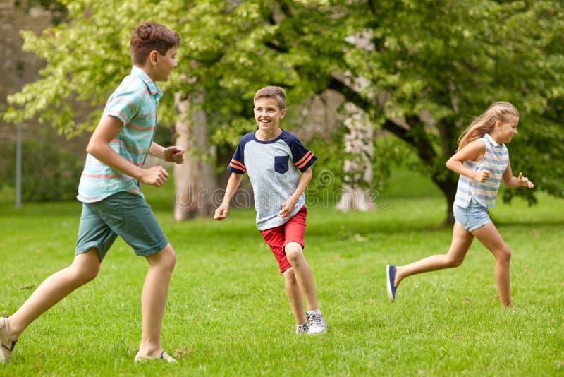 Crianças felizes que correm e que jogam o jogo fora foto de stock