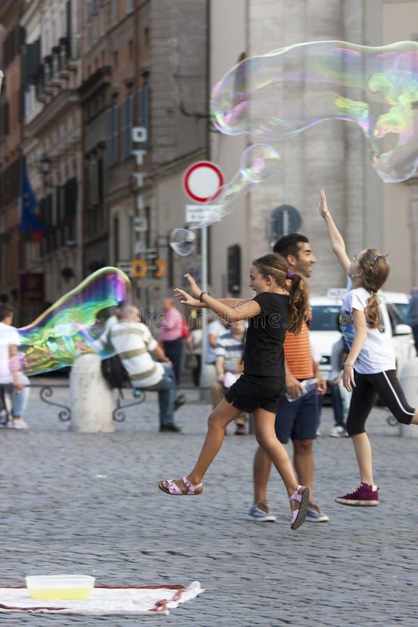 Crianças felizes que correm para uma bolha de sabão fotografia de stock