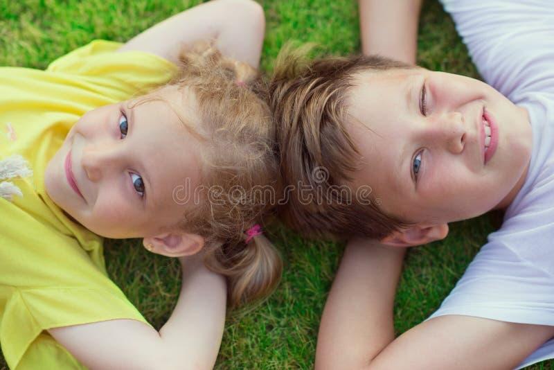 Crianças felizes que encontram-se na grama verde no quintal fotografia de stock