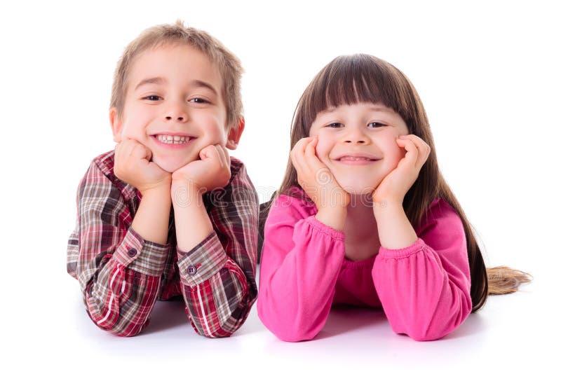 Crianças felizes que encontram-se no branco fotografia de stock royalty free