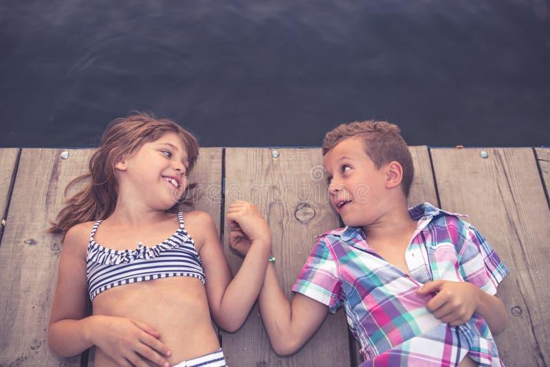 Crianças felizes que encontram-se no cais de madeira e que guardam as mãos imagens de stock royalty free