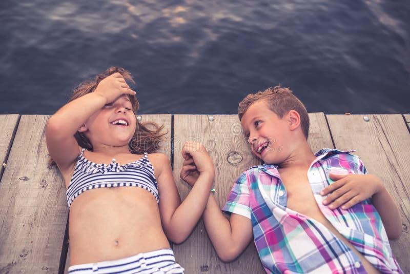 Crianças felizes que encontram-se no cais de madeira e que guardam as mãos foto de stock royalty free
