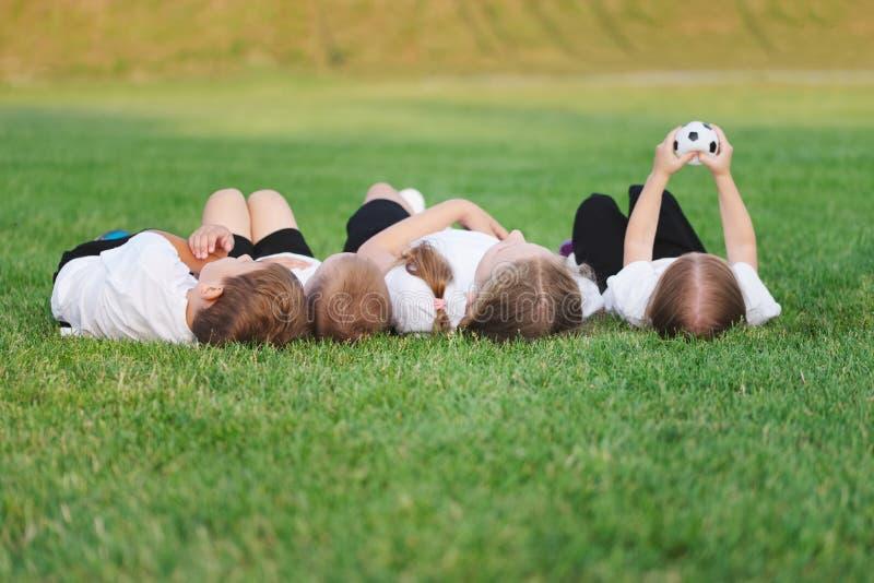Crianças felizes que encontram-se no passo de futebol imagem de stock