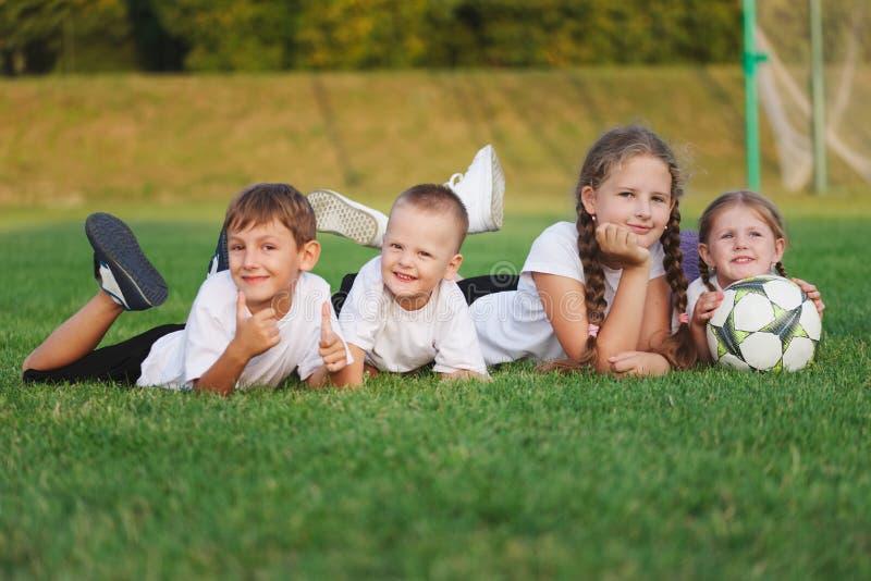 Crianças felizes que encontram-se no passo de futebol fotografia de stock royalty free