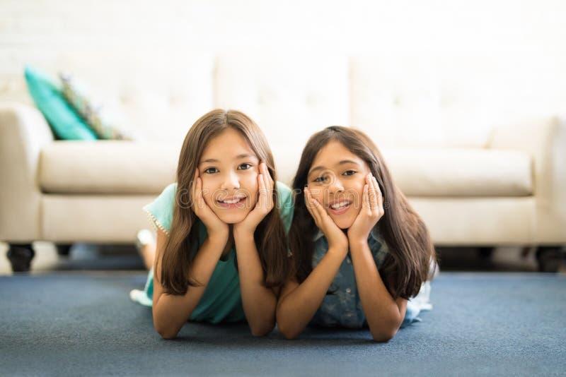 Crianças felizes que encontram-se no tapete imagem de stock
