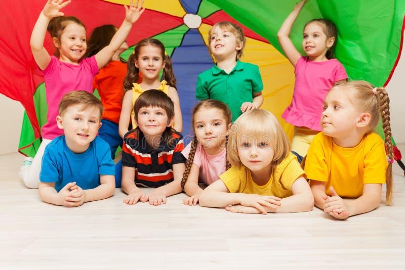 Crianças felizes que escondem sob a barraca feita do paraquedas fotografia de stock