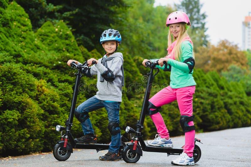 Crianças felizes que estão no 'trotinette' bonde exterior foto de stock royalty free