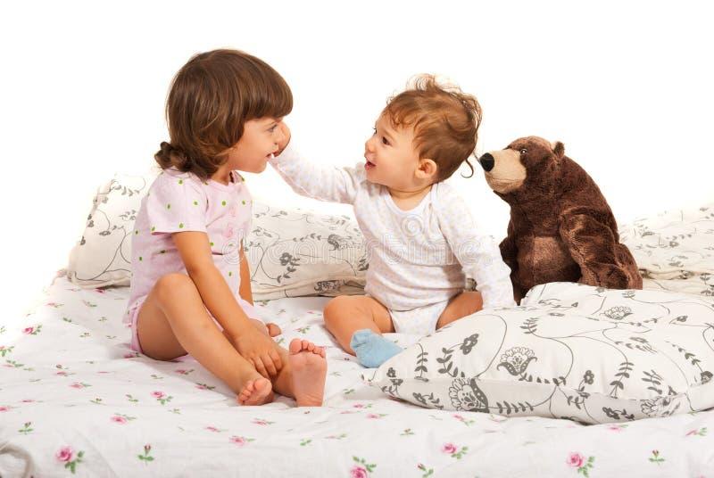 Crianças felizes que falam na cama fotografia de stock royalty free