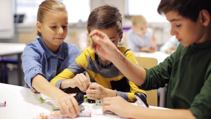 Crianças felizes que fazem a elevação cinco na escola da robótica vídeos de arquivo