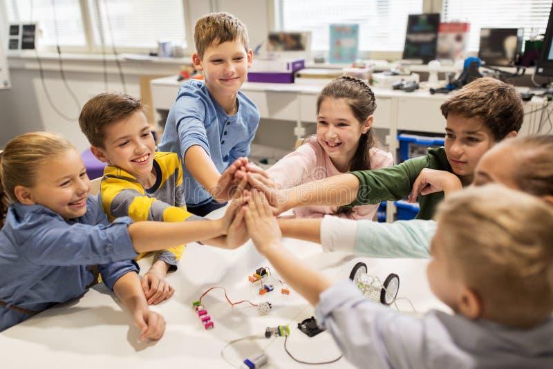 Crianças felizes que fazem a elevação cinco na escola da robótica fotos de stock