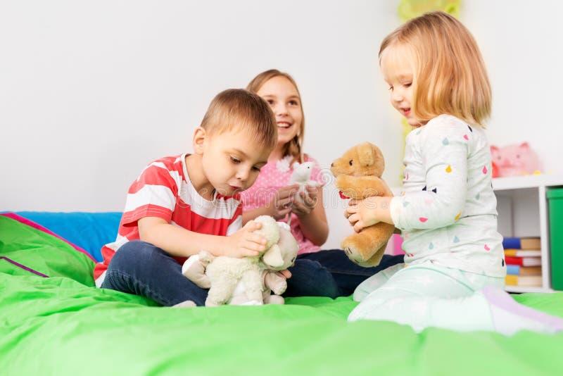 Crianças felizes que jogam com brinquedos macios em casa imagem de stock