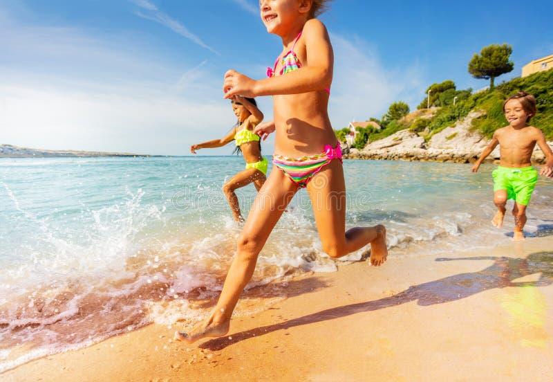 Crianças felizes que jogam competindo jogos na praia imagem de stock royalty free