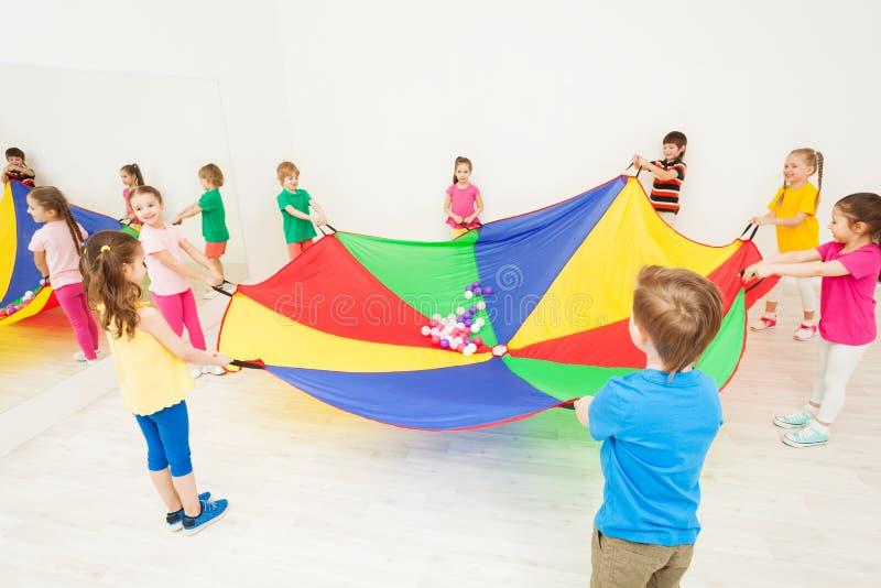 Crianças felizes que jogam jogos do paraquedas no gym imagem de stock royalty free