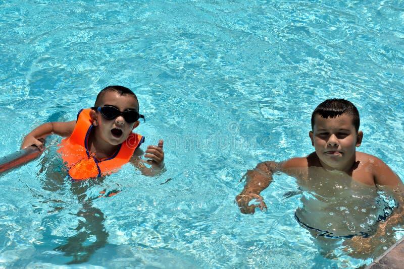 Crian?as felizes que jogam na piscina foto de stock