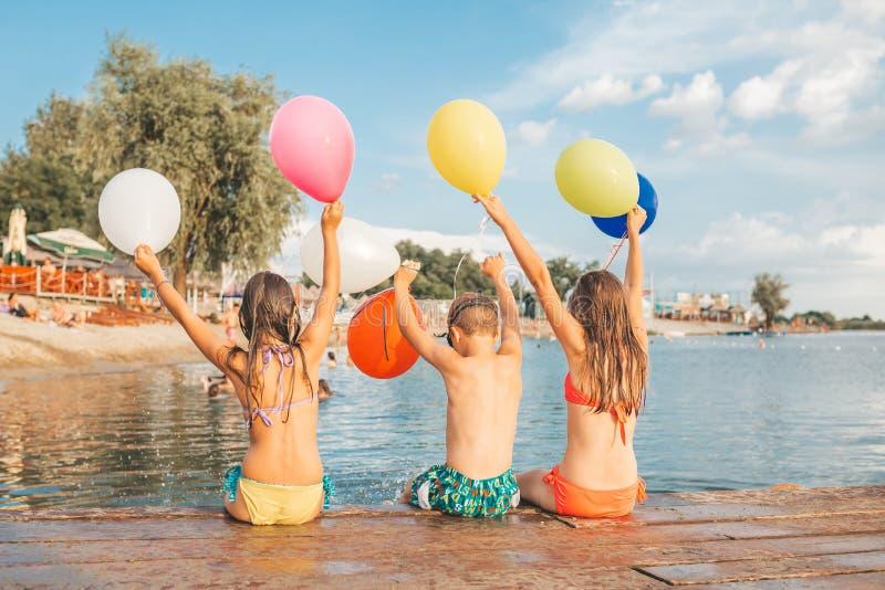 Crianças felizes que jogam na praia com balões imagem de stock