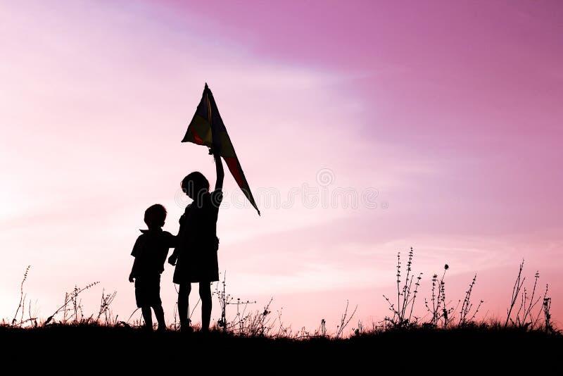 Crianças felizes que jogam na silhueta do verão da natureza fotos de stock royalty free