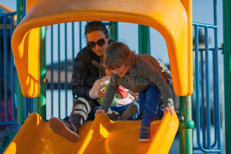 Crianças felizes que jogam no parque com sua mãe fotos de stock