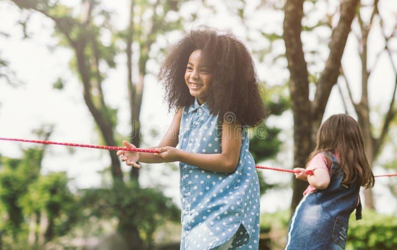 Crianças felizes que jogam o conflito no parque fotografia de stock
