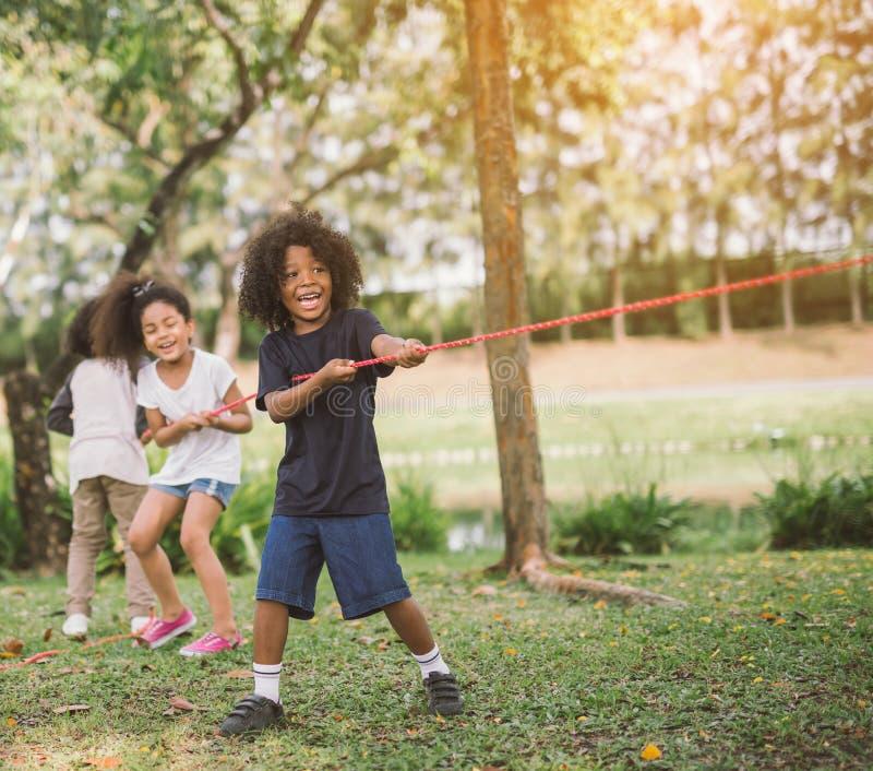 Crianças felizes que jogam o conflito no parque imagens de stock