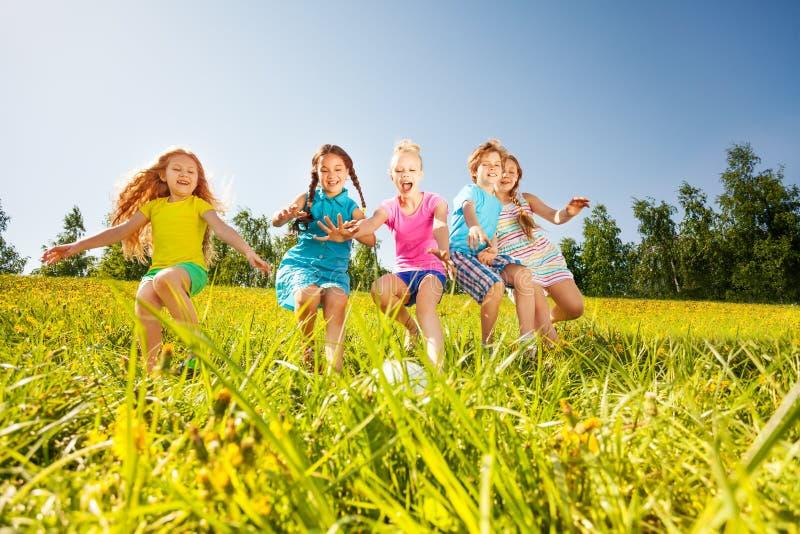 Crianças felizes que jogam o futebol no prado amarelo foto de stock royalty free