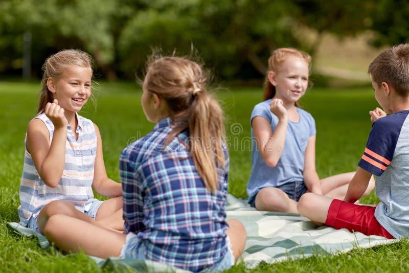 Crianças felizes que jogam o jogo das rocha-papel-tesouras foto de stock
