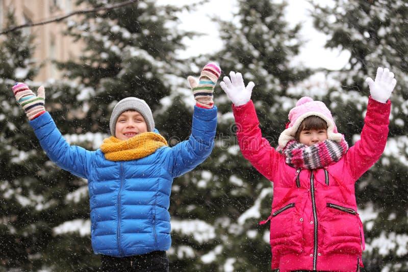 Crianças felizes que jogam perto dos abeto cobertos com a neve imagens de stock
