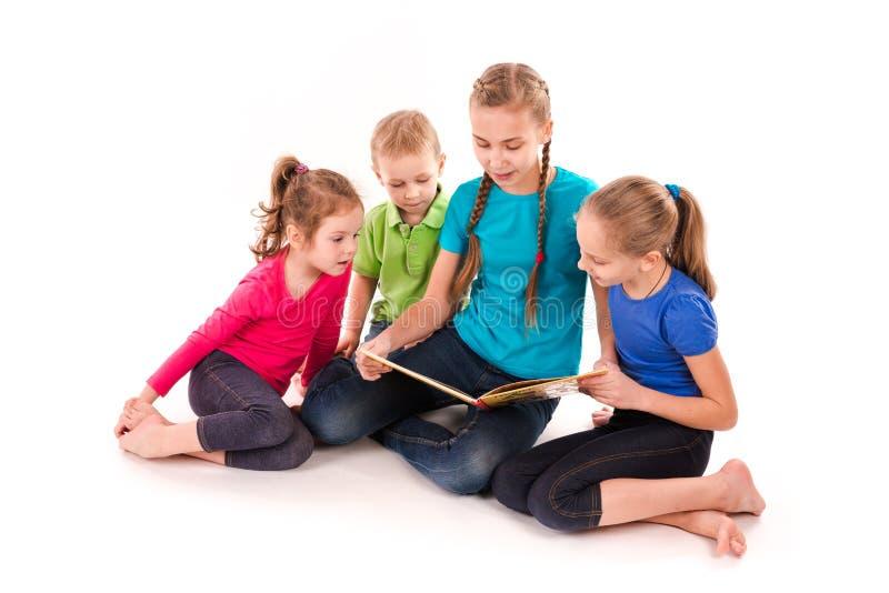 Crianças felizes que leem um livro isolado no branco foto de stock royalty free