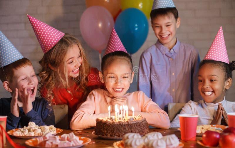 Crianças felizes que olham o bolo de aniversário com velas foto de stock