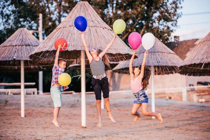 Crianças felizes que saltam com balões fotografia de stock