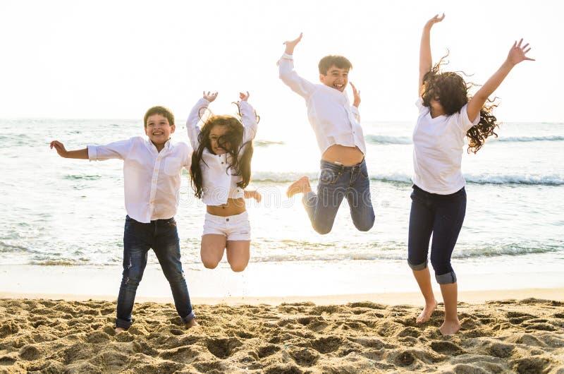 Crianças felizes que saltam junto na praia imagens de stock royalty free