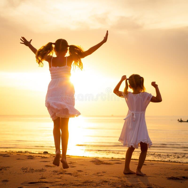 Crianças felizes que saltam na praia imagem de stock