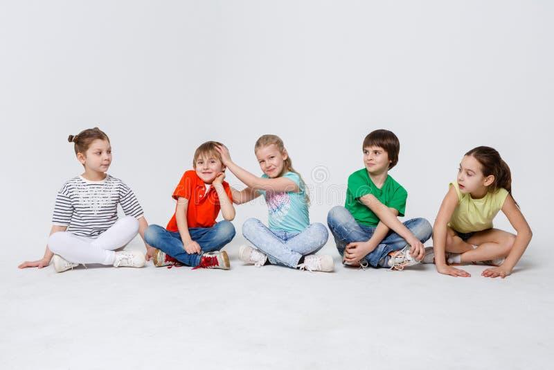 Crianças felizes que sentam-se no assoalho no estúdio, espaço da cópia fotos de stock royalty free