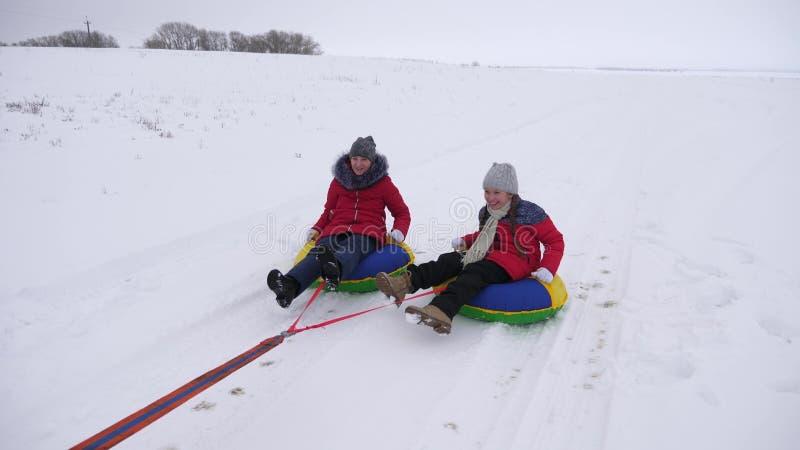 Crianças felizes que sledding no inverno na neve e que acenam suas mãos as crianças riem e exultam menina que joga no inverno fotos de stock royalty free