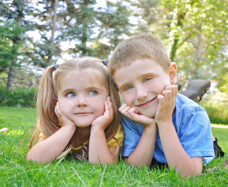 Crianças felizes que sorriem na grama verde imagem de stock royalty free