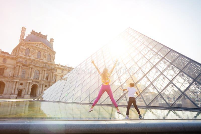 Crianças felizes que têm o divertimento em Paris perto do Louvre famoso em férias francesas fotos de stock