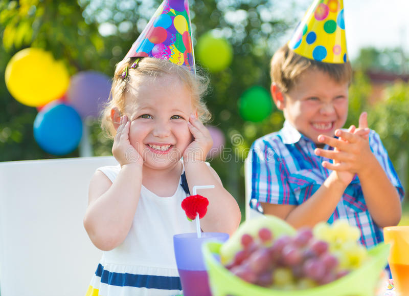Crianças felizes que têm o divertimento na festa de anos foto de stock royalty free