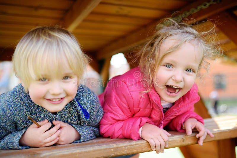 Crianças felizes que têm o divertimento no campo de jogos exterior fotos de stock