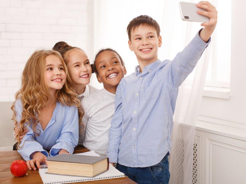 Crianças felizes que tomam o selfie na sala de aula da escola imagem de stock