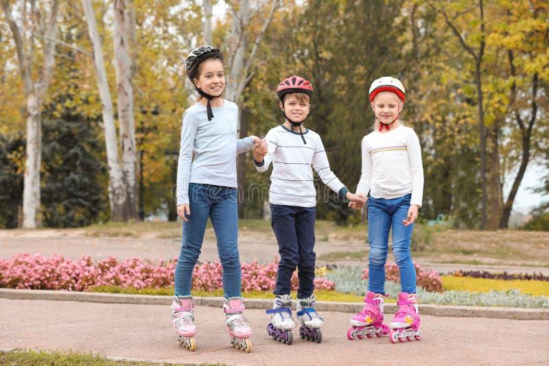 Crianças felizes que vestem patins de rolo imagem de stock royalty free